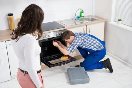 repairman fixing the oven