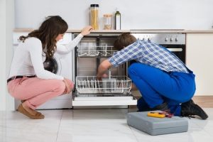 repair man fixing dishwasher